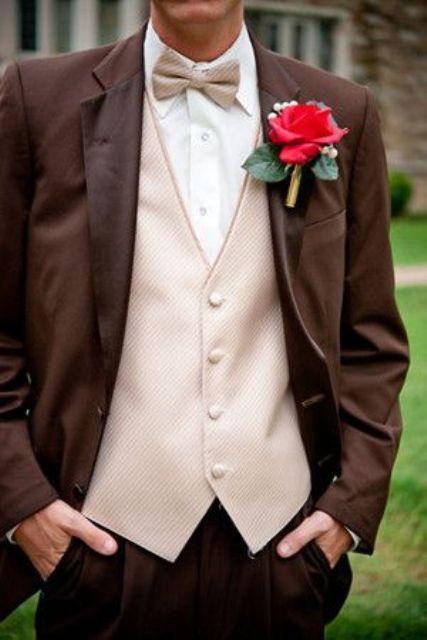 a brown suit, a neutral waistcoat and a matching bow tie plus a large floral boutonniere