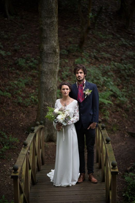 a navy suit, a white button down. a plum colored vintage tie, brown shoes and a greenery boutonniere for a winter woodland wedding