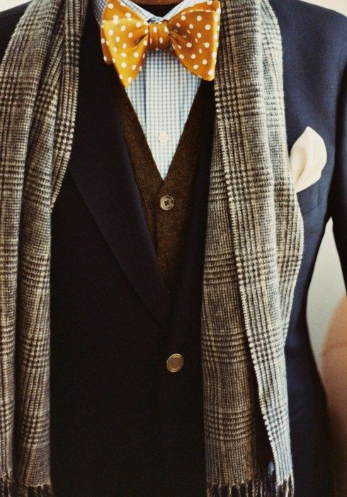 a navy tweed suit, a brown waistcoat, a printed shirt and a yellow polka dot bow tie, a grey checked scarf for a catchy winter look
