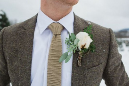 a grey tweed suit, a white button down, a neutral tie and a cotton boutonniere to feel warm on a cold day