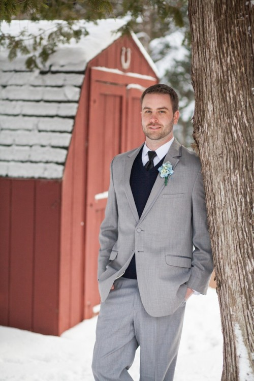 a grey suit, a black jumper over the shirt, a black tie and a white button down for an elegant and chic winter groom's look