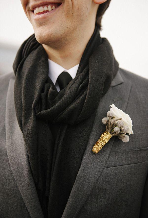 a grey suit, a black scarf, a white button down and a black tie plus a cotton boutonniere