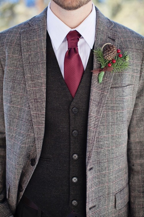 a grey checked tweed suit, a black waistcoat, a burgundy tie, a white button down and a pinecone and berry boutonniere