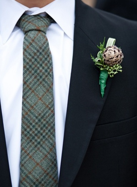 a black velvet suit, a white button down, a green plaid tie and a pinecone boutonniere