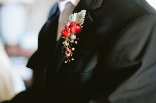 a black suit, a white button down, a black tie, a berry boutonniere plus pale greenery