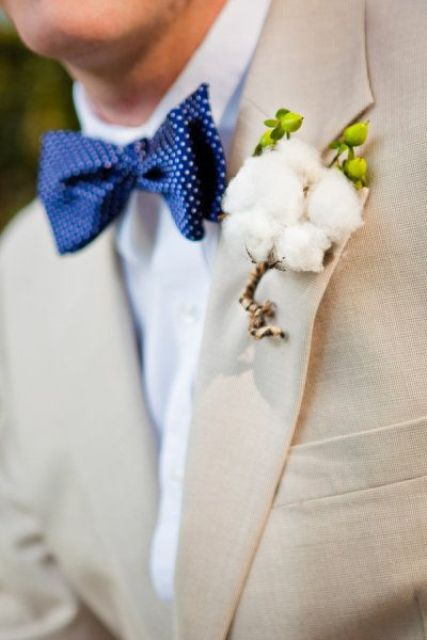 a creamy suit, a white shirt, a navy bow tie with polka dots, a cotton boutonniere