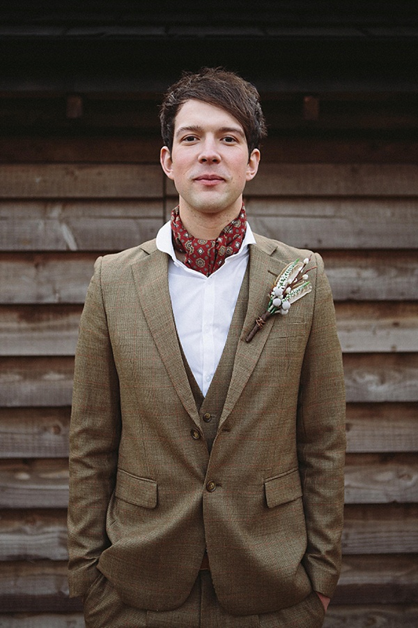 a brown three piece wedding suit, a white button down, a red neck tie and a boutonniere
