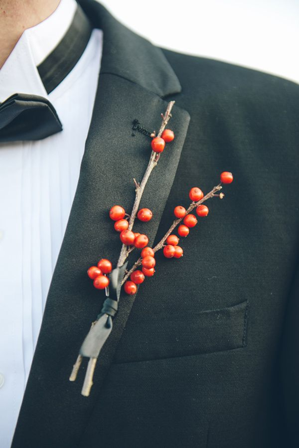 a classic black tux highlighted with a red berry boutonniere is a timeless winter groom's outfit