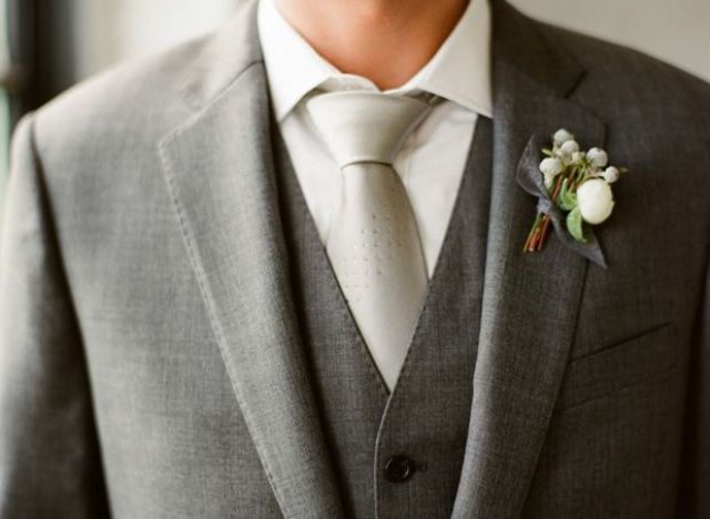 a grey three piece suit, a white button down, a shiny silver tie and a white floral boutonniere