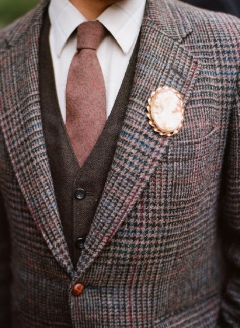 a brown plaid tweed suit, a brown waistcoat, a white button down, a mauve tie and a vintage brooch boutonniere