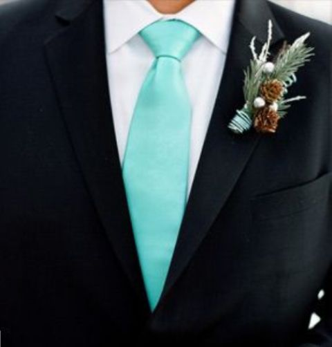 a black suit, a white button down, a mint green tie and a winter boutonniere with pinecones and evergreens