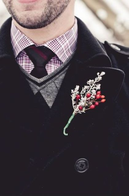 a checked button down, a burgundy tie, a jumper over the shirt and a black coat plus a boutonniere for an outdoor ceremony or portrait