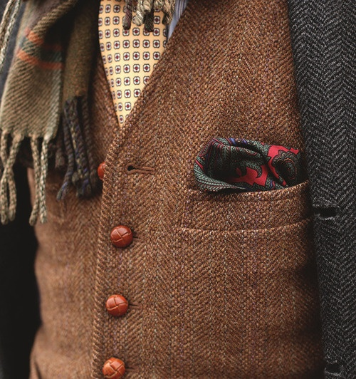 a printed shirt and tie, a brown tweed waistcoat, a grey tweed blazer plus a scarf for a catchy look