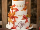 a cute fall wedding or bridal shower cake with calligraphy and bright fall leaves plus small pumpkins on top