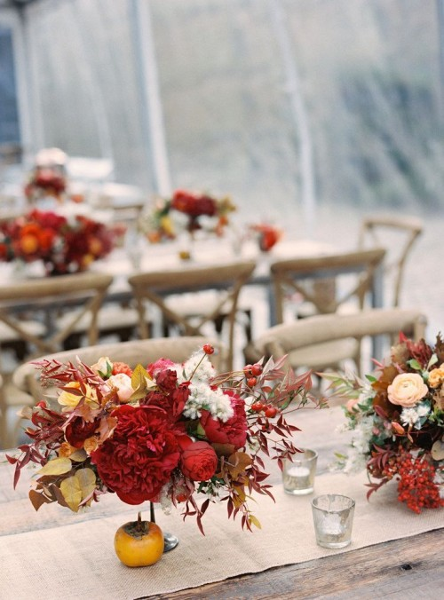 a chic and bold fall bridal shower centerpiece of deep red blooms, foliage and some berries