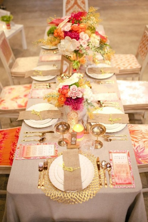 a bright and glam fall bridal shower tablescape done with bold floral arrangements, gold touches, colorful menus and burlap napkins