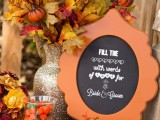 a bright faux foliage, pumpkins and berry arrangement and a chalkboard sign for a fall bridal shower