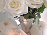 a chic centerpiece of white roses, white pumpkins and candles can be easily DIYed