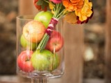 a cute fall bridal shower centerpiece of apples and a bright blooms arragement