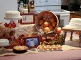 a fall bridal shower dessert table with cute cakes, tarts, apples and cupcakes plus hay for a rustic feel