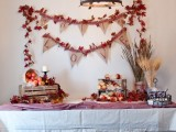 a fall bridal shower station decorated with bright leaves, apples and dried herbs in crates and baskets for a rustic feel