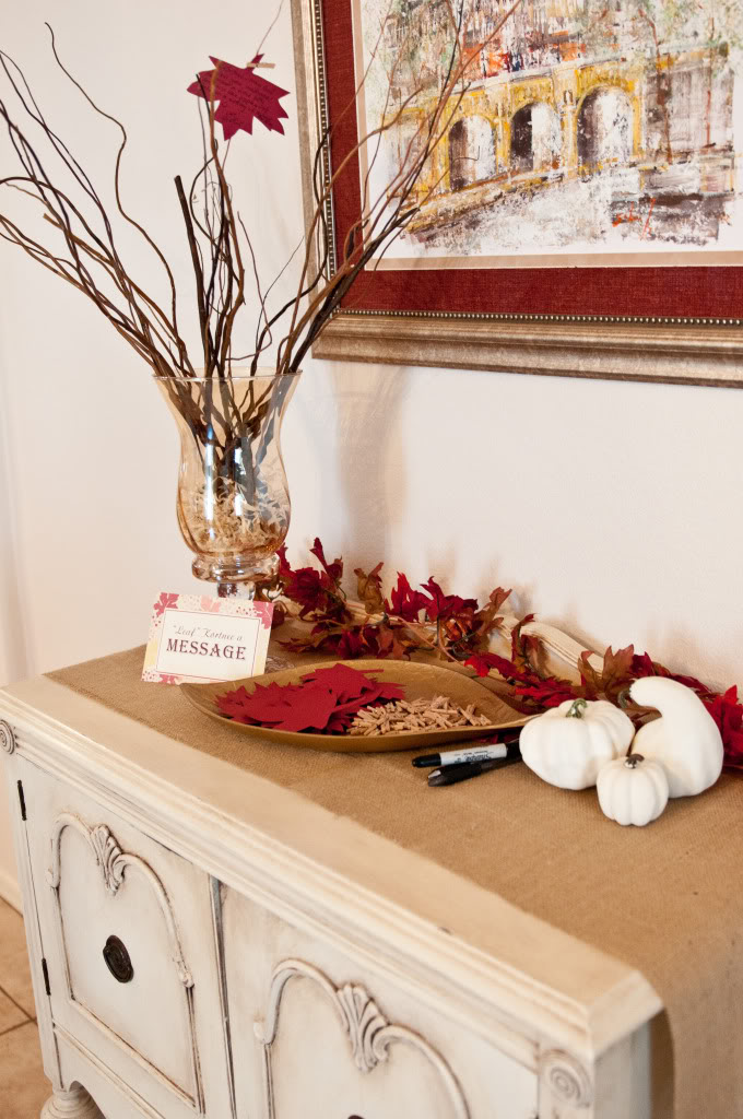 a fall bridal shower station decorated with burlap, pumpkins and bright paper leaves