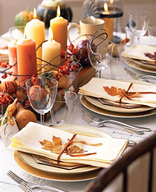 a chic fall bridal shower tablescape with a neutral tablecloth, a cool centerpiece of faux pumpkins, pinecones, gourds, candles and fall leaves