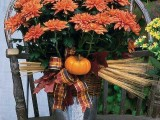a rustic fall decoration of a bucket, a plaid ribbon, dried herbs and a faux pumpkin plus bright fall blooms