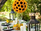 a fall bridal shower tablescape with candles, candle lanterns, bright sunflower decor