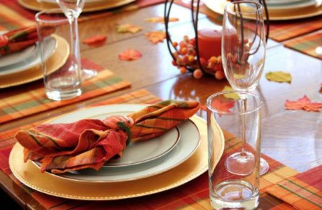 a bright fall bridal shower table setting with colorful plaid placemats, napkins and colorful candles