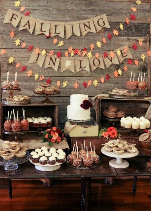 a rustic fall bridal shower dessert bar with leaves, a burlap banner and lots of fall-themed treats and sweets