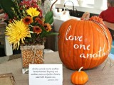 a fall centerpiece of bright blooms and corn and a large orange pumpkin with white letters for a fall bridal shower centerpiece