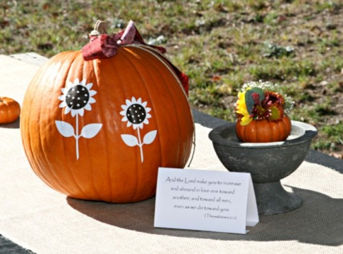 an orange pumpkin with painted sunflowers is a cool fall bridal shower decoration or centerpiece