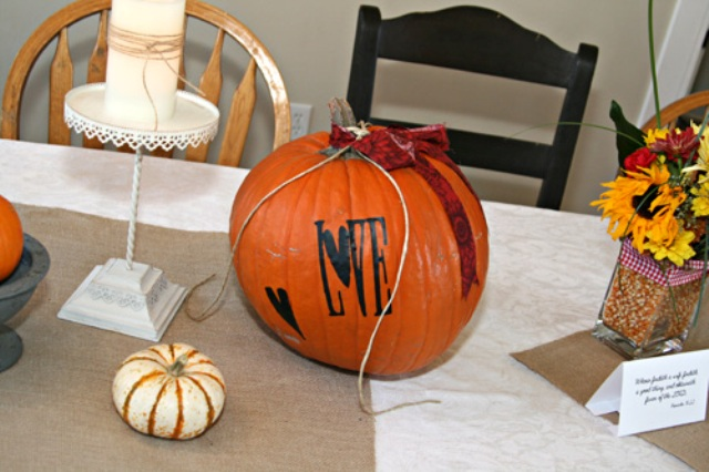 an orange pumpkin with letters, ribbons and painted elements is a great decoration for the shower