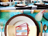a bold place setting done in turquoise, burgundy and orange plus woven chargers
