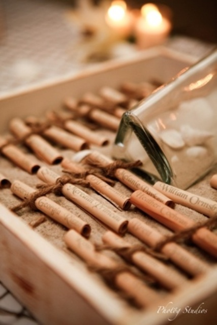 a wooden box with beach sand, a bottle and letters of paper with names on them is a creative way to display escort cards