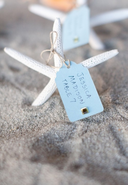 a box with beach sand and starfish with escort cards is great for a beach or coastal wedding