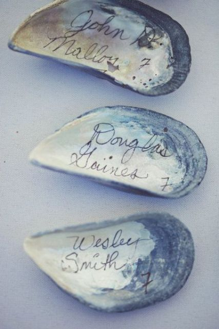 simple DIY escort cards made of shells using a sharpie is an easy idea suitable for every beach or coastal wedding