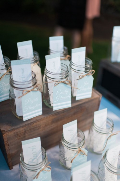 jars on wooden boxes with escort cards and tags with yarn bows are cool for any wedding