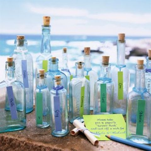 blue bottles with names written on tags is a nice idea to display wedding escort cards for a beach wedding