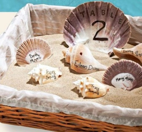 a basket with beach sand and mismatching seashells and names written on them is a nice option for a beach celebration