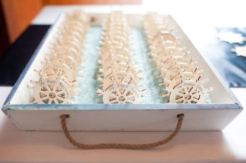 a tray with aqua seaglass and steering wheels with names is a cool decoration and they can double as favors