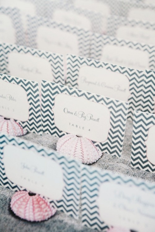 a tray with beach sand, pink sea urchins with chevron escort cards is a chic and elegant way to display escort cards