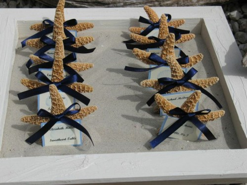 a tray with sand, starfish with ribbon bows and escort cards is a simple option to display escort cards for a nautical wedding