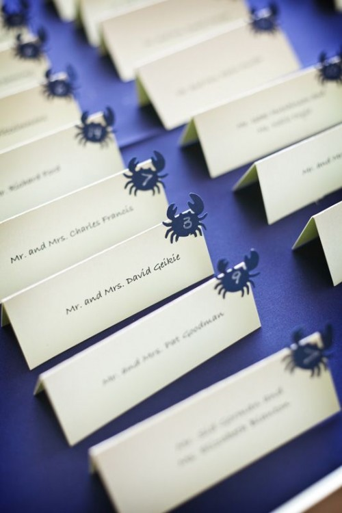 a purple tray with escort cards and little crabs is a stylish and simple DIY for a beach wedding