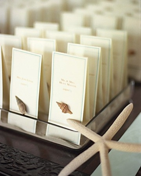 a glass tray with beach sand and escort cards with little seashells attached is a very chic and timeless idea