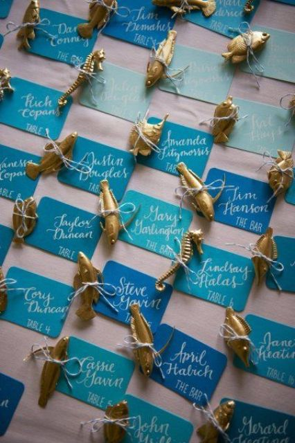 bright escort cards in all shades of blue and with sea creature figurines attached is a very bold and fresh idea