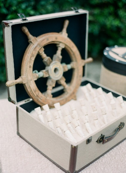 a box with beach sand, escort cards in test tubes and a steering wheel for a nautical wedding