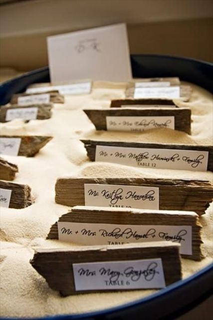 a blue porcelain bowl with beach sand and driftwood escort cards is a cool wedding seating chart