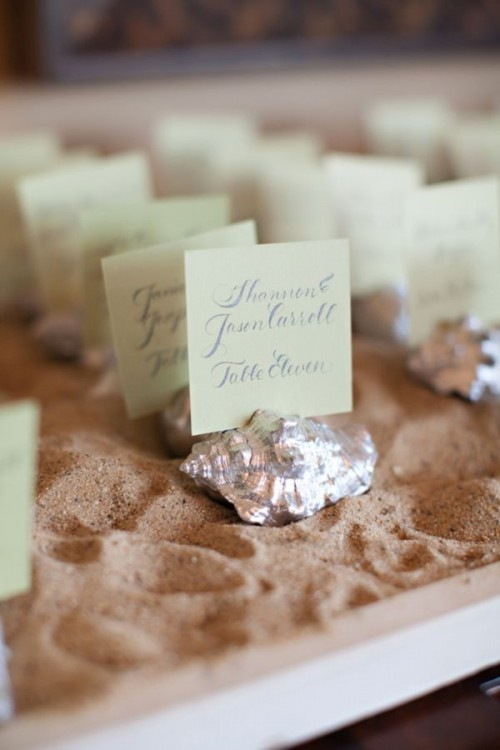 a tray with beach sand, silver seashells and escort cards attached to the them is a cool idea for a beach wedding
